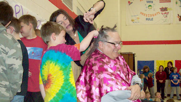 Michelle Carnago helps students ¿snip, snip, snip¿ Principal Tom Hausbeck¿s  hair.