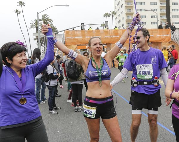 Julie Weiss, center, completed her 52nd marathon in 52 weeks. With her is fiance David Levine and six-month pancreatic cancer survivor Lupe Romero.