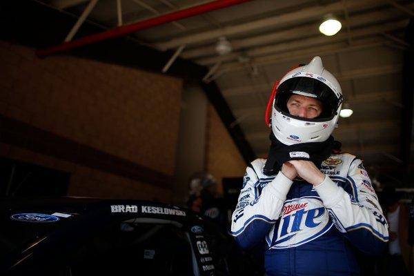 Brad Keselowski stands in the garage during practice for the NASCAR Auto Club 400.