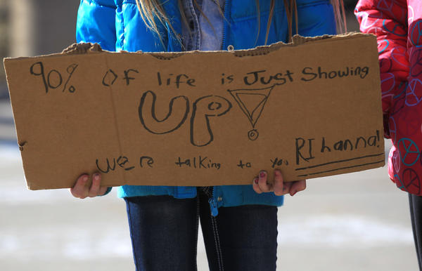A student holds a sign with a message for pop music star Rihanna, who was late showing up for her appearance at Barrington High School. Rihanna came to the school after the students won a video contest.