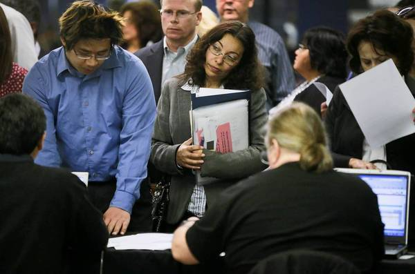 Applicants seeking work stand in line at the 10,000 Best Jobs Expo at Angel Stadium in Anaheim. The one-day job fair was organized by the National Employment Council.