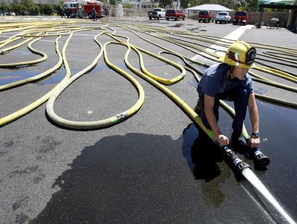 Burbank Fire Station 12 firefighter Brandon Vaughan releases trapped air from fire hoses.