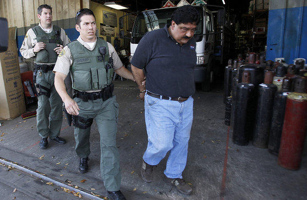 L.A. County sheriff's deputies escort a suspect after a raid on Victory Welding & Supply in South Los Angeles on Friday.