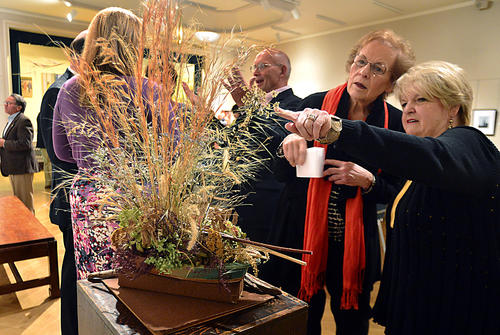 "Ann Law and Patty Powley, both of Hagerstown, admire the floral design created by the Mt. Airy Garden Club inspired by the photograph called ""Highway 12-Hatteras North Carolina"" by Bruce Wilder Friday during the reception for the annual Art in Bloom event at the Washington County Museum of Fine Art organized with the Hagerstown Garden Club."