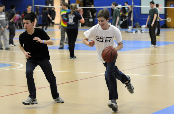Ryan Kaelin, 14, dribbles past Christopher Copeck, 14. The students could play basketball, video dance games, badminton, listen to music or perform musical skits when not helping pack meals.