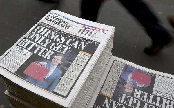 Commuters walk past copies of the London Evening Standard newspaper.