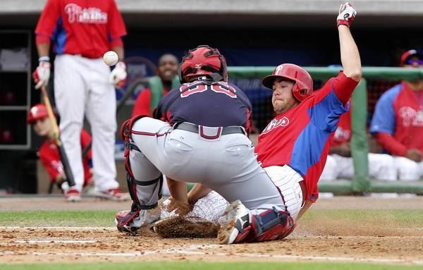 March 22, 2013; Clearwater, FL, USA; Philadelphia Phillies left fielder Darin Ruf (18) slides safely into home plate as Atlanta Braves catcher Evan Gattis (68) misses the ball during the second inning at Bright House Networks.