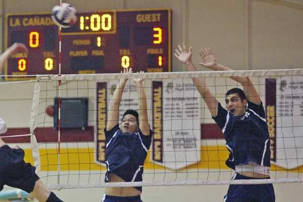 Flintridge Prep's Mike Lii, from left, and Kareem Ismail go up for a block in a match at La Cañada High.
