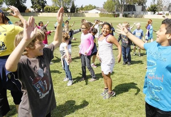 Students, from kindergarten through sixth grade, do jumping jacks during lunchtime at California Elementary on Friday.