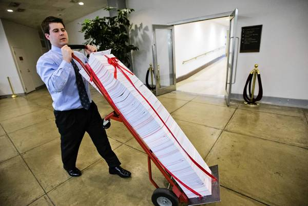 A Senate aide delivers a stack of documents to be used as a prop during debate on the chamber's budget proposal.