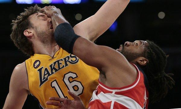 Wizards big man Nene smacks Lakers forward Pau Gasol across the face during a jump ball during the first half.