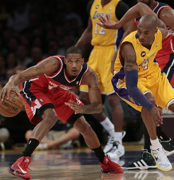 Wizards forward Trevor Ariza dribbles around Lakers defender Kobe Bryant during the first half.