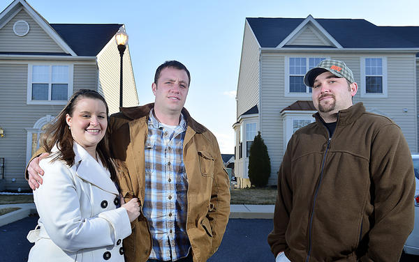 Heather Kurtz and Jesse McAllister, left, and Steven Mazur stand in front of their neighboring townhomes in Hager's Crossing west of Hagerstown.