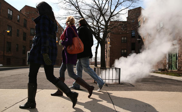 From left, Diana Burke, Allison Burke and Ted Ehrhardt walk past a steam vent near the intersection of West Diversey Parkway and North Leavitt Street as temperatures rose near the 40s prior to a spring snowfall that is expected overnight in Chicago.