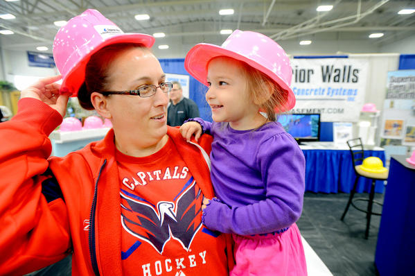 Hagerstown residents Angela Nallo and her daughter Alexis, 2, put on their matching pink plastic construction hats Saturday at the HCC Home Show. The hats were courtesy of Superior Walls.