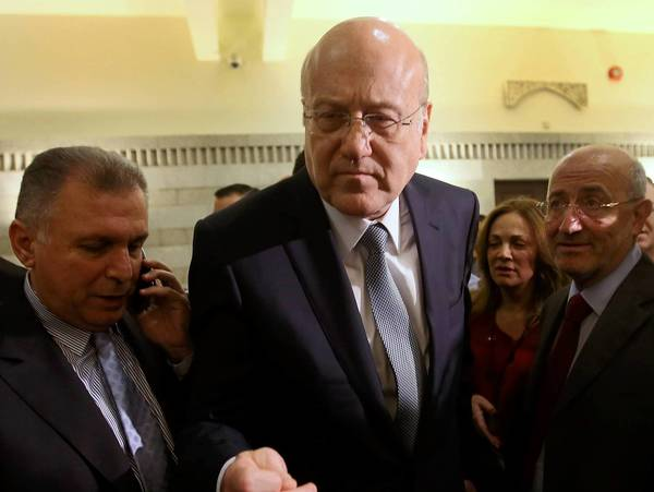 Lebanese Prime Minister Najib Mikati, center, announced his resignation late Friday. He will continue to head a caretaker government until a replacement is named.