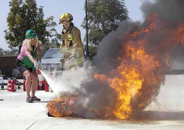 Newport Beach firefighter Matt Skelly gives instruction to Maureen Downey on how to put out a fire with a fire extinguisher during the Newport Beach Fire Department's CERT event Saturday at the Santa Ana Heights station No. 7.