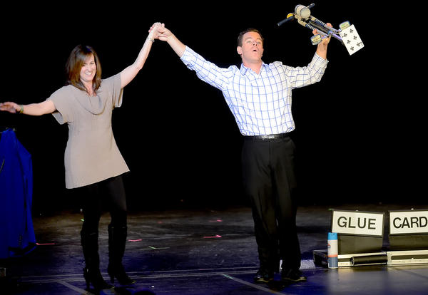 Friends of Safe Place Treasurer Jodi Blair, left, takes a bow with Magician and Comedian Eric Buss after the two performed a card trick Saturday night at The Maryland Theatre in downtown Hagerstown.