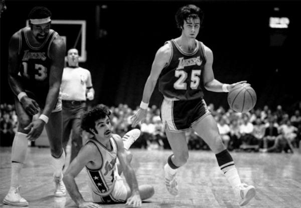 Lakers' Gail Goodrich gets away from Dave Wohl of the Philadelphia 76ers after Wohl trips over Wilt Chamberlain.