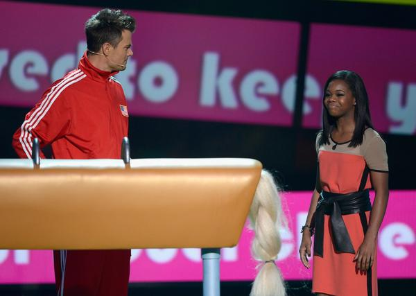 Host Josh Duhamel stands next to  the pommel horse as gold medal-winning Olympic gymnast Gabby Douglas looks on.