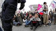 Demonstrators sit in near the Arc de Triomphe during a protest march over France's planned legalization of same-sex marriage