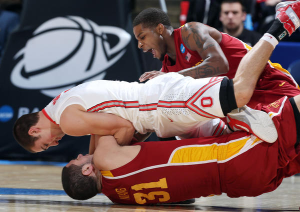Ohio State Buckeyes guard Aaron Craft (4) battles for a loose ball on top of Iowa State Cyclones forward Georges Niang (31) while guard Korie Lucious (13) assists during the third round of the 2013 NCAA tournament at University of Dayton Arena.