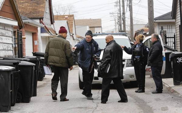 An evidence technician, second from left, a police officer, second from right, and detectives investigate the shooting of a 14-year-old boy on 37th Street at S. Hamilton Avenue.