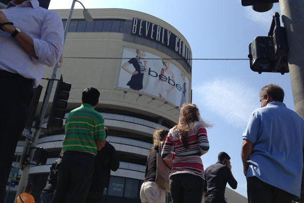 People look on after an evacuation of the Beverly Center in Los Angeles due to a suspicious package report.
