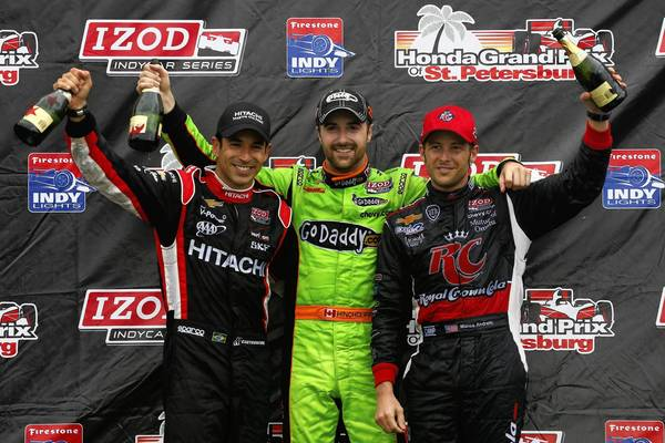 James Hinchcliffe of Canada (center), driver of the GoDaddy.com Andretti Autosport Dallara Chevrolet stands on the podium with second-place finisher Helio Castroneves of Brazil, driver of the Hitachi Team Penske Chevrolet and third-place finisher Marco Andretti, driver of the RC Cola Andretti Autosport Chevrolet, following his victory in the IZOD IndyCar Series Honda Grand Prix of St Petersburg.