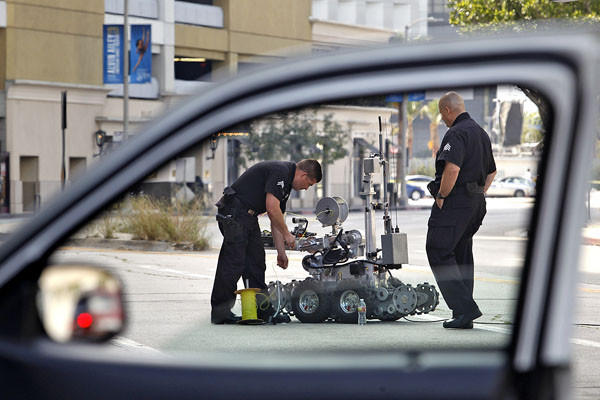 LAPD officers use a robot at the Beverly Center in Los Angeles after the shopping mall was evacuated when a suspicious package was found Sunday in the attached parking garage.