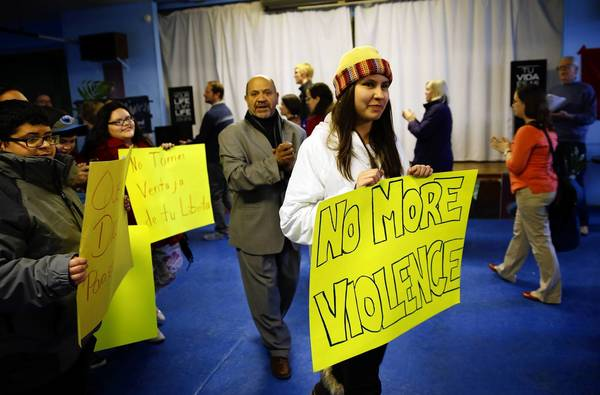 """Noemi Wilson, 13, walks with her """"No More Violence"""" sign as a program begins at a Palm Sunday rally and get together to address issues of community concerns seen here at St. Luke's Church in Logan Square. The rally addressed issues including youth disconnection, mass incarceration, deportations, street violence, homelessness, poverty, hunger and militarism and the work being done by various congregations."""