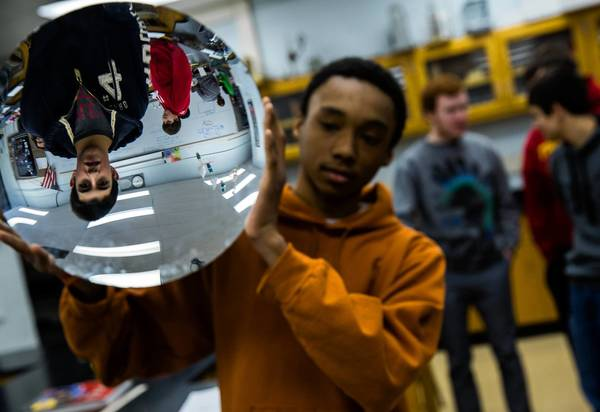 Matthew Jones, 15, holds a mirror for an optics lesson in ninth-grade honors physics at Tinley Park High School.