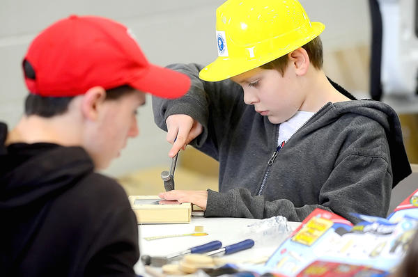 Coby Rubeck, 11, of Hagerstown works on his fun house mirror project with a hammer Sunday morning during the annual Home Show at the Hagerstown Community College's Athletic, Recreation and Community Center.
