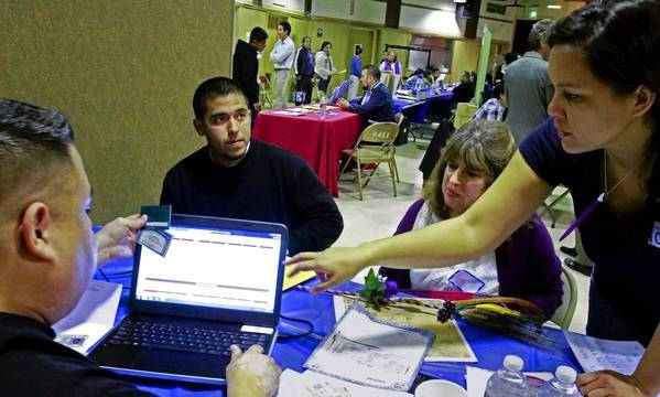 Volunteers Edward Chavez, left, and Cori Racela, right, work on enrolling Alan Servin and his mother Ana Soltero, 54, in healthcare coverage at an L.A. County event at La Placita Church in Los Angeles.