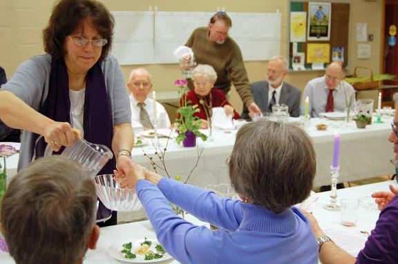 Jeanne Fulk of Frederick, Md., helps Sue McMorris of Chambersburg, Pa., wash her hands during a Jewish-Christian seder held Sunday at Church of the Apostles in Waynesboro, Pa.