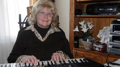 Sue Miller playing the keyboard she uses in her monthly singalongs. Both the keyboard and the singalongs were gifts from her late husband.