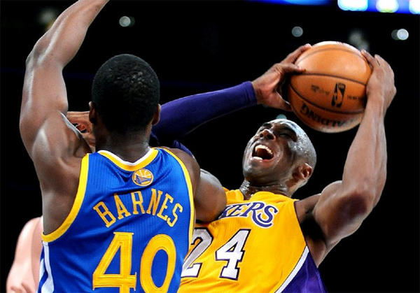 Lakers guard Kobe Bryant, right, attempts a shot over Warriors forward Harrison Barnes.
