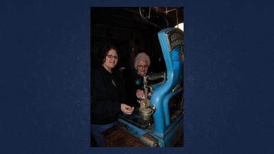 Director in charge Carol Cook (left) and honorary director Janet Susser weigh peanuts on an antique scale.
