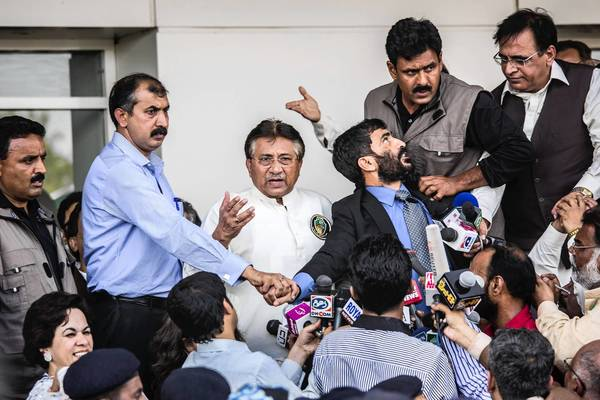Former Pakistani President Pervez Musharraf, in white, addresses a crowd at the international airport in Karachi.