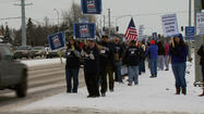 More than a hundred postal workers and supporters braved the cold and snow and held a rally against plans to cut Saturday delivery service at busy intersection in Anchorage.