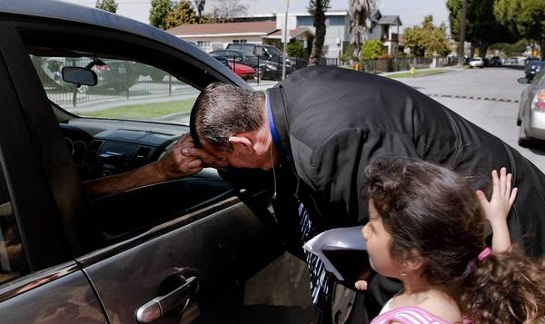 Pastor and former Bell City Councilman Luis Artiga,with his daughter Sarah, 7, by his side, clutches a parishioner's hand through a car window after he gave his sermon at Bell Community Church. The congregation was overjoyed and thankful for his acquittal on 12 charges of misappropriation of public funds in the city's salary scandal.