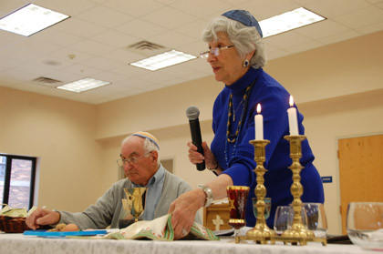 Bea Premack, right, speaks about the story of Passover as her husband, Herschel Premack, follows along. The two were from B'Nai Isaac Synagogue and told the story of Passover to a group of more than 100 people Sunday at St. Mary's Catholic Church.