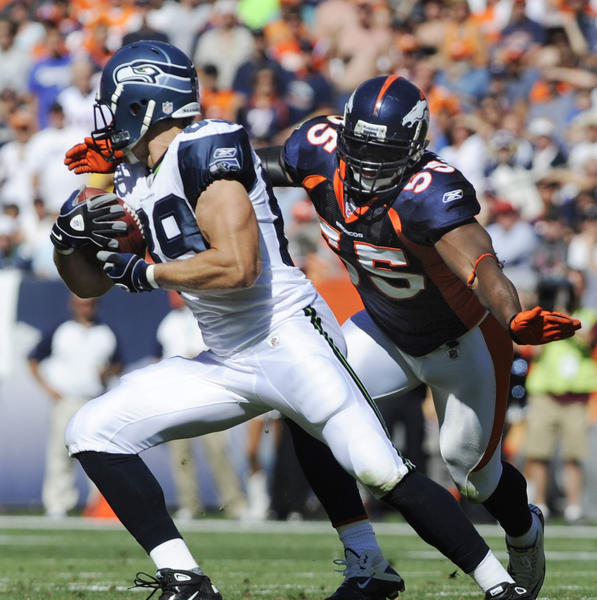 Linebacker D.J. Williams brings down Seahawks tight end John Carlson during a 2010 game.