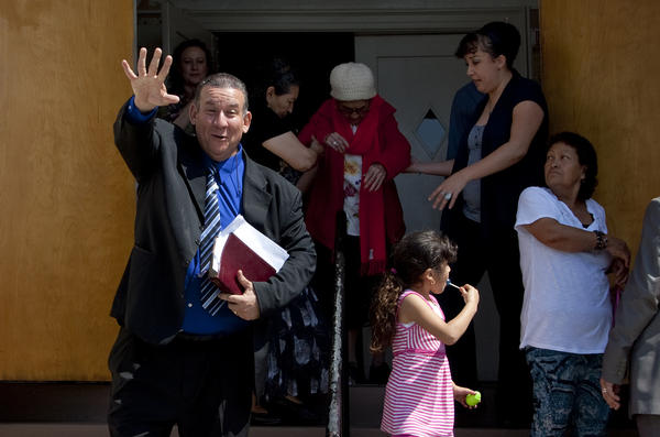 Pastor Luis Artiga, a former Bell councilman, clutches his Bible and waves to a church member after giving his sermon at the Bell Community Church on Sunday.