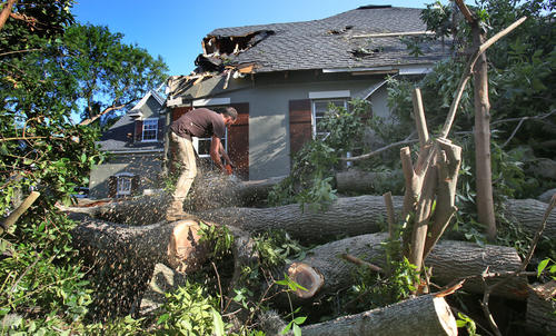 After a violent storm swept through Windermere Sunday Dustin Davidson of Emergency Services & Reconstruction uses a chainsaw   Monday to remove a tree that fell on a home on Pine St. in Windermere.  (Red Huber / Orlando Sentinel)