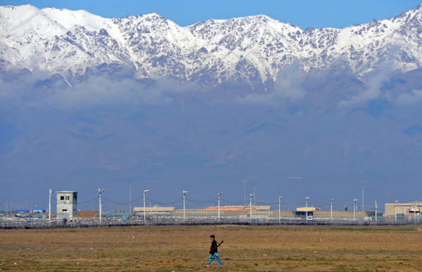 An Afghan man carries a gun as he walks past Bagram prison facilities outside Kabul. Afghanistan took full control of the detention facility from the United States.