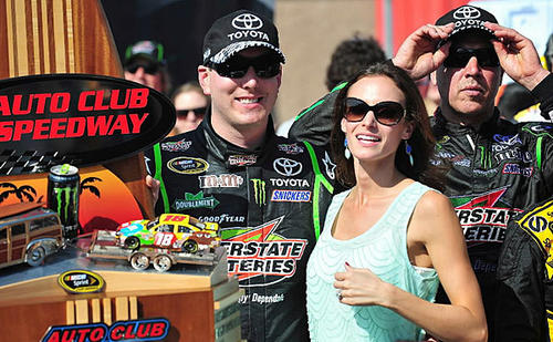 NASCAR driver Kyle Busch and his wife, Samantha, enjoy the winner's circle after his win in the Auto Club 400.