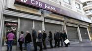 People line up to make transactions at an ATM machine outside a closed Cyprus Popular Bank (CPB) branch in Athens