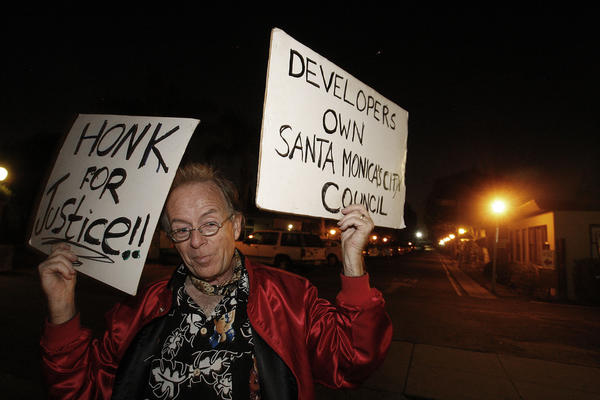 Peter Naughton, 63, holds protest signs in front of the Village Trailer Park in Santa Monica. He has lived in the park since 1991; his trailer home has been in his family since 1986.