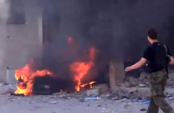In an image from video, a building burns after government shelling near Damascus, the Syrian capital. The United Nations announced it is temporarily withdrawing staff from the war-torn nation because of safety concerns.